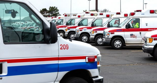 Rows of ambulances are parked outside.